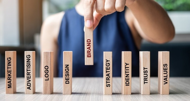 businesswoman-hand-placing-or-pulling-wooden-dominoes-with-brand-text-and-marketing-advertising-logo_t20_YwXeLX (1) (1)