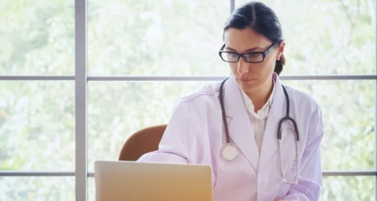 doctor-with-stethoscope-working-writing-on-paperwork-with-clipboard-and-laptop-computer-on-table-in_t20_P3bvJr (1)-1