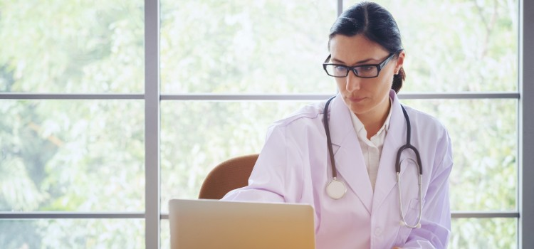 doctor-with-stethoscope-working-writing-on-paperwork-with-clipboard-and-laptop-computer-on-table-in_t20_P3bvJr (1)