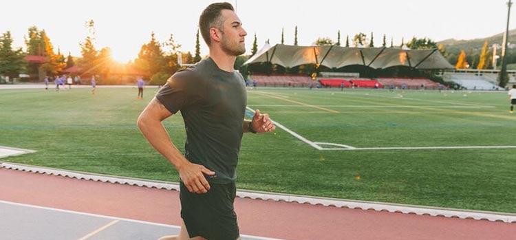 man-running-on-track-at-sunset