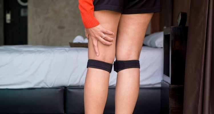 woman-wearing-knee-brace-with-legs-female-putting-bandage-on-her-injured-knee_t20_OzQbBE (1)